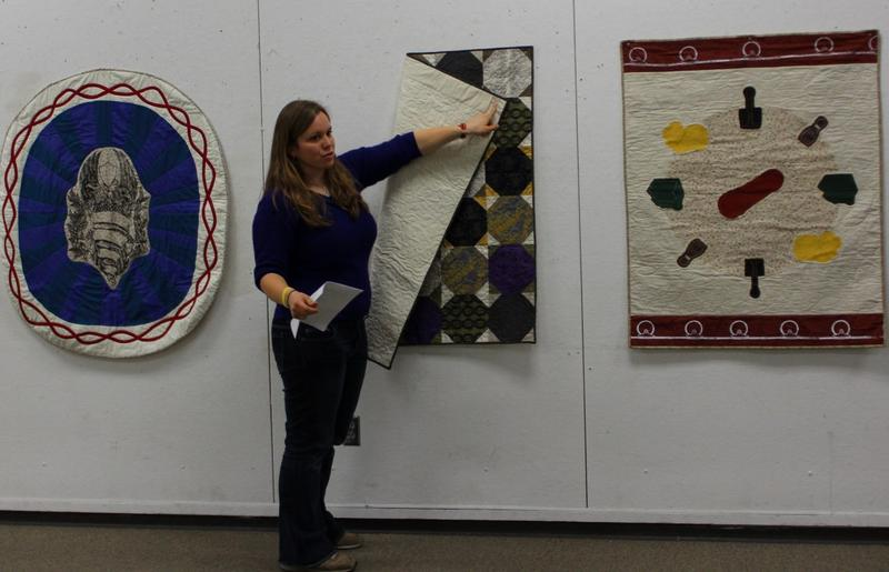 "KU graduate student Sarah Podrasky says she ""was invested in the quilt designs"" she helped create. Here, she points out one with circuitry-inspired fabric."
