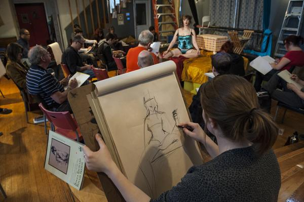 Stephanie Maximovich holds her sketchpad as she works on a drawing.