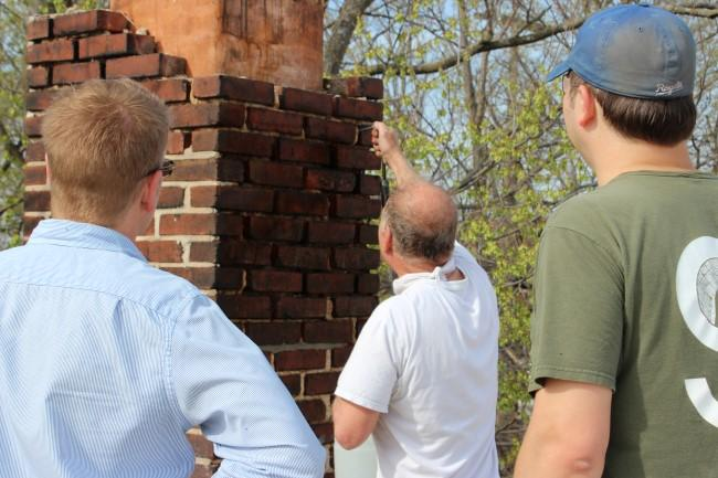 Butch Rigby (at left) and Jeremy Knoll (at right) observe as master mason, Dan Stewart, demonstrates tuck pointing technique.