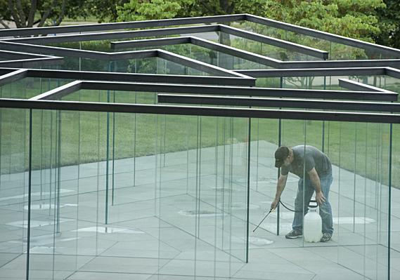 Before Morris' arrival, Ed Devaney, of TDC, Ltd. cleans the foundation of 'Glass Labyrinth,' the newest addition to the Donald J. Hall Sculpture Park at the Nelson-Atkins Museum of Art.