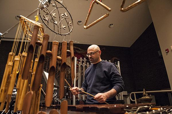 Surrounded by triangles and chimes, Petrella plays the xylophone.