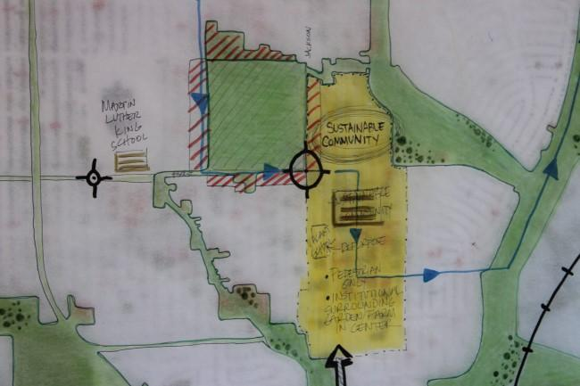 """A close-up of green spaces on a map called """"Blue River Country Fingers."""" It's placed on top of a vacant land map, with Land Bank properties in red."""