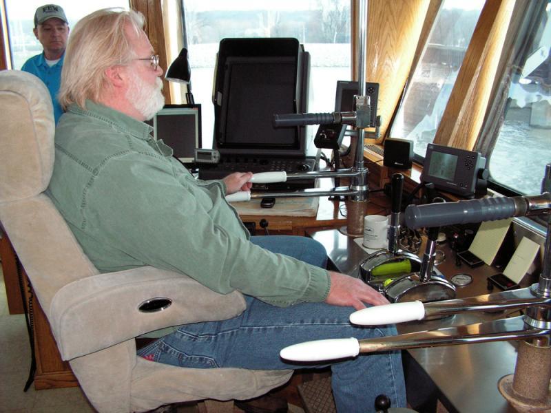 Luke Moore, captain of the Crimson Glory, steers it down the Illinois River near Peoria, Ill.