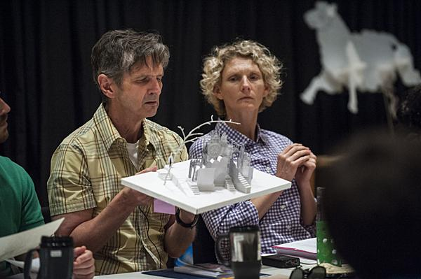 Actor Bruce Roach (at left) and choreographer and movement coach Tracy Terstriep take a closer look at a three-dimensional model of the set on the first day of rehearsal.