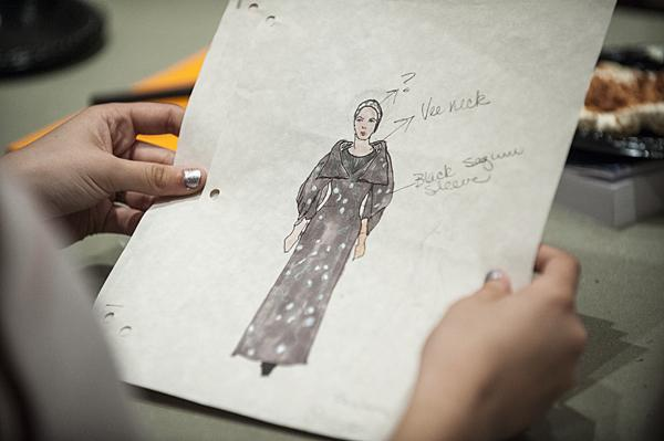 Sketches of the costumes are passed from actor to actor.