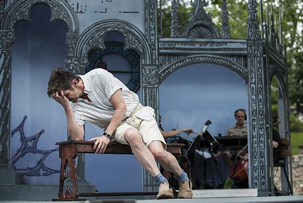 Overcome with paranoia, King Leontes (Bruce Roach) collapses on a bench.