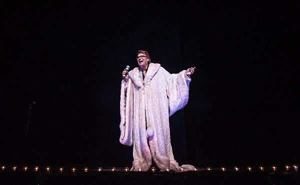 Commenting on the expense of his robe, Martin Preston as Liberace makes a grand entrance.
