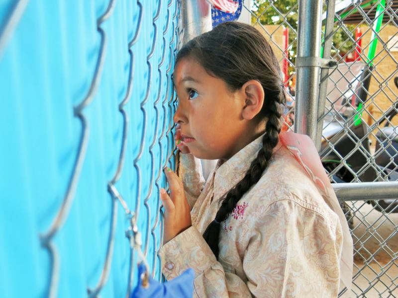 Navaeha Salgado, 6, peers through a fence at the Greeley Stampede to scope out the sheep she'll soon be latching onto and riding around the arena.