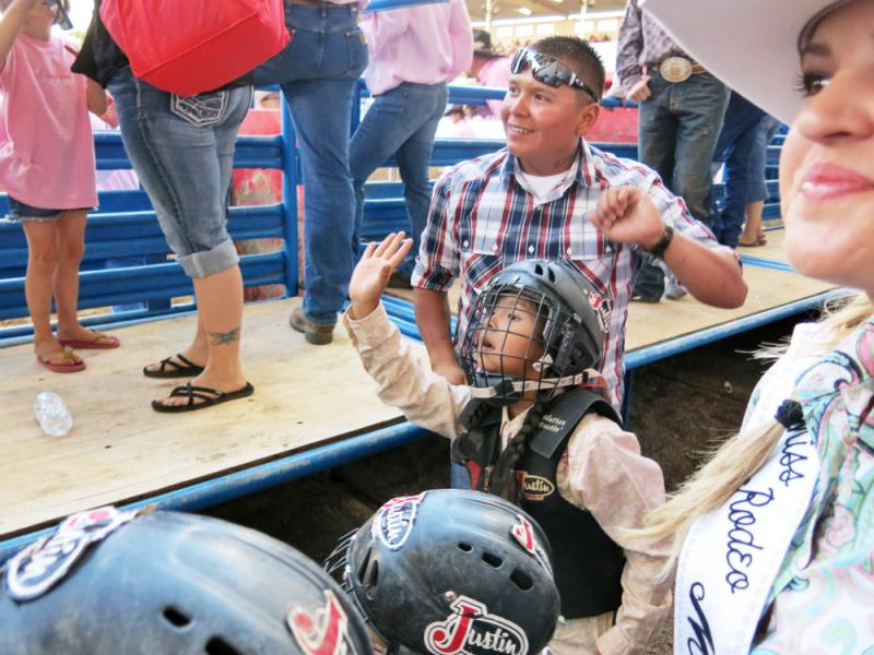 Contestant Navaeha Salgado waves to her mother in the stands while her father, Dominic Salgado, looks on. The children who participate in mutton busting are required to wear a protective vest and helmet, and parents sign waivers.