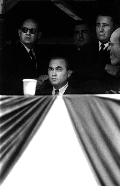 Alabama segregationist and Governor, George Wallace with political henchmen surveys crowd at counrty stadium before political rally.