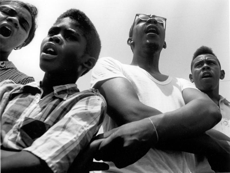 Summer volunteers, SNCC workers and local students singing freedom songs at Mileston, a community of independent black farmers in the Mississippi Delta near Lexington.