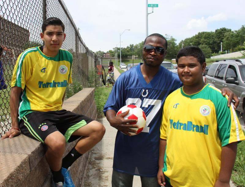 Angel Ponce, of Mexico, Jean-Luc Kamin, of the Ivory Coast, and Soemoe Oo, of Burma, all play soccer with Coach Foday Kamara.