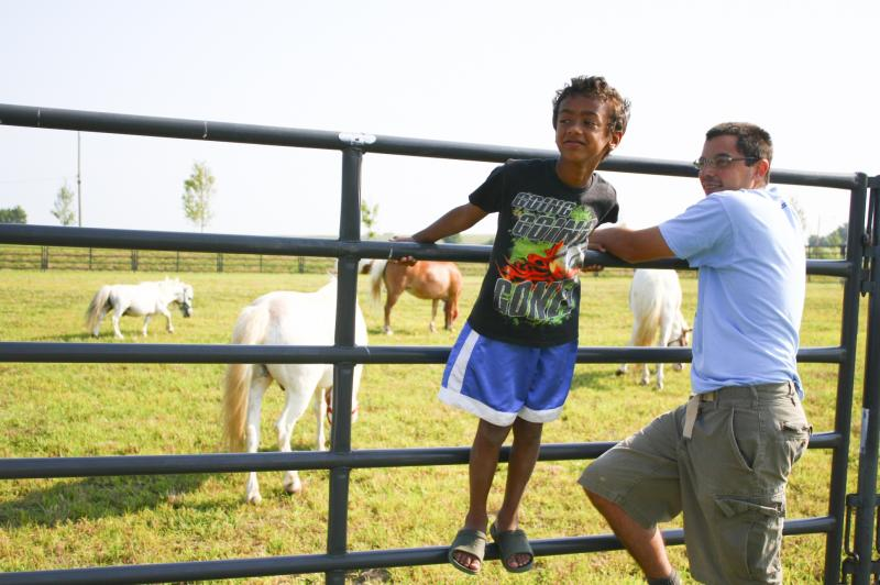 A father and son enjoy the pony corral.