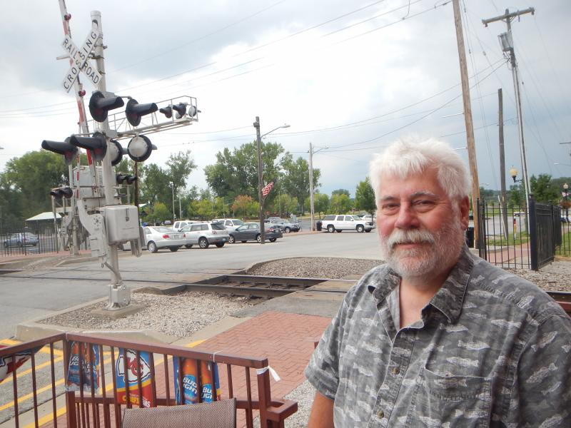 Dust expert Greg Muleski on the terrace of a restaurant in the Kansas City suburban city of Parkville. The restaurant is a few feet from a level crossing where coal trains cross the town's main street.