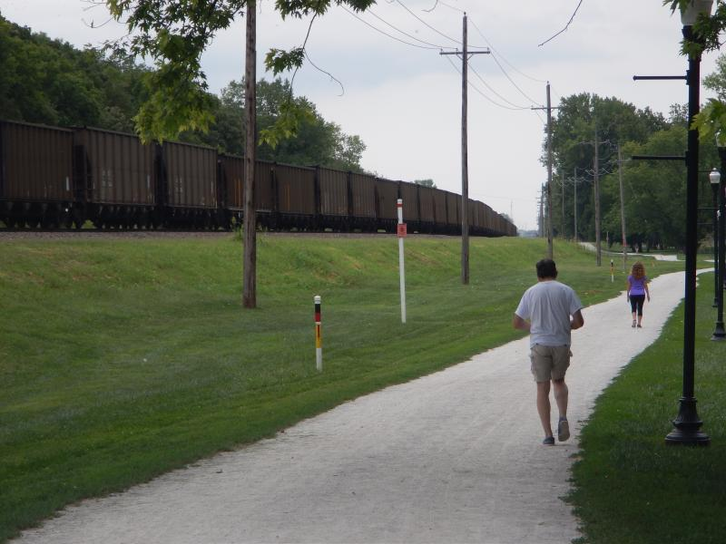 Two joggers enjoy Parkville's recreational area as a coal train passes them by.
