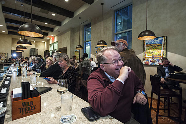 Tom Woolwine sits at the bar speaking with friends during the reopening of JJ's restaurant.