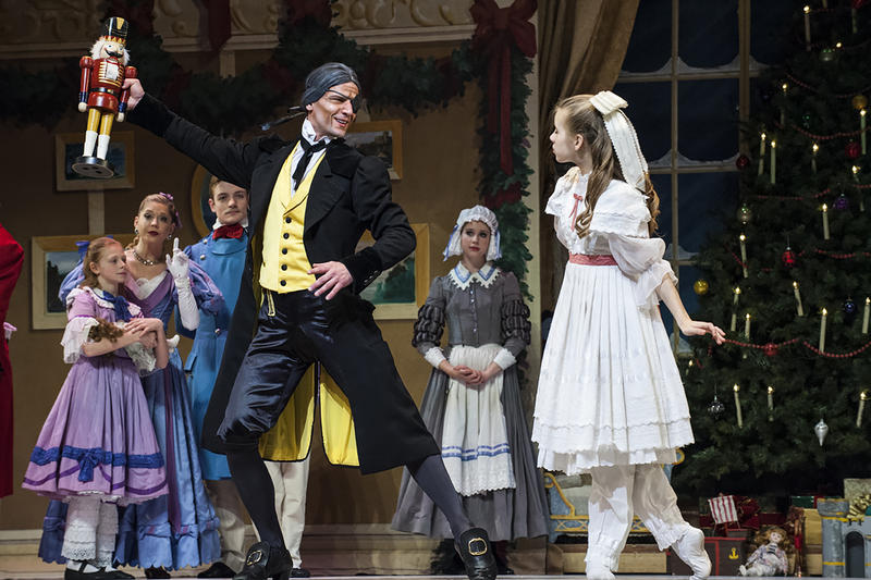 Logan Pachciarz (Drosselmeyer) holds aloft a toy nutcracker for all to see.
