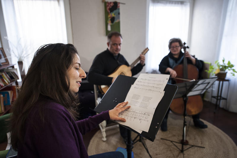 Soprano Victoria Botero keeps an eye on the verses as she rehearses 'The Darkest Midnight,' one of the best known carols -- one that is sung on Christmas Day.