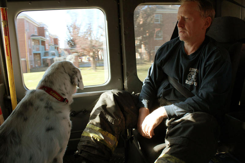 Firefighter Kimble Cowan sits with station dog Lucky.