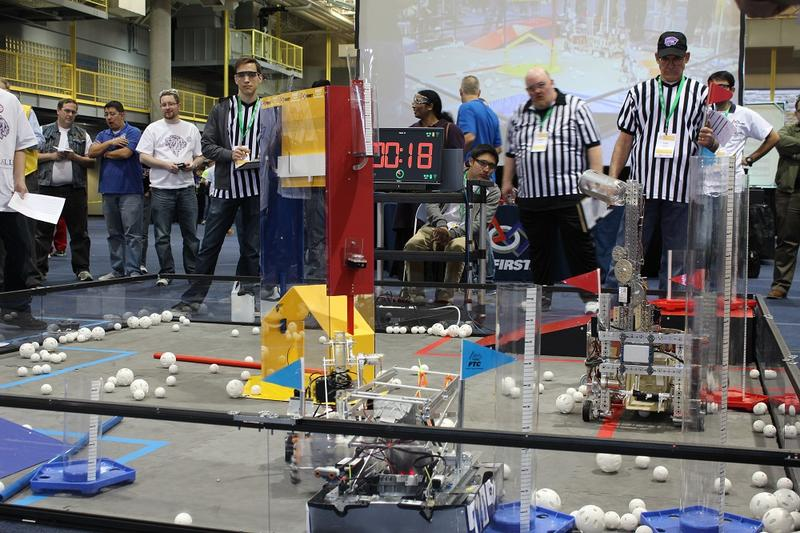 Student built robots attempt to capture wiffle balls and put them in tall bins at the FIRST Tech Challenge qualifier.
