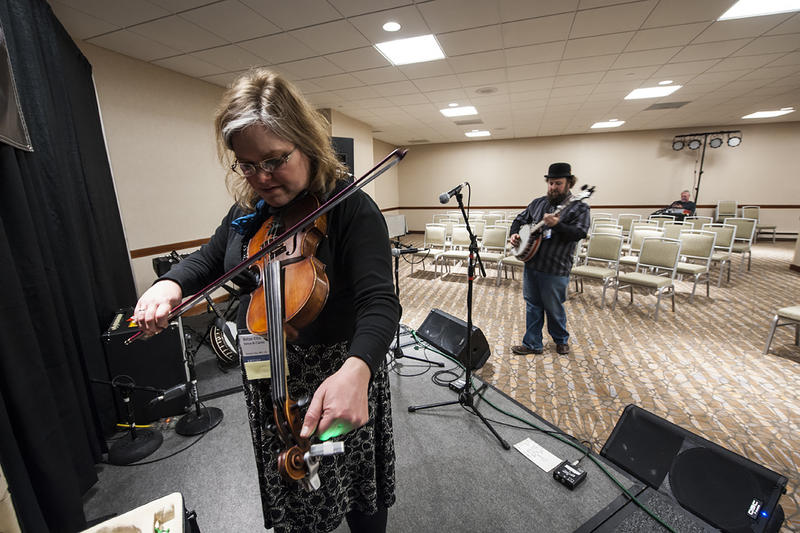 Betse Ellis tunes up as Clarke Wyatt rehearses behind her. The fiddle and banjo duo  'Betse & Clarke' performs Ozark tunes both new and old.