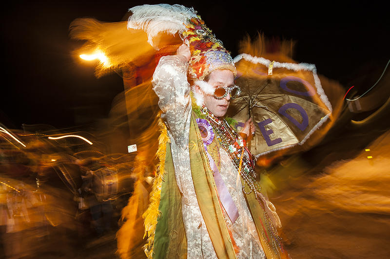 A merrymaker bedecked with beads marches into the night air.