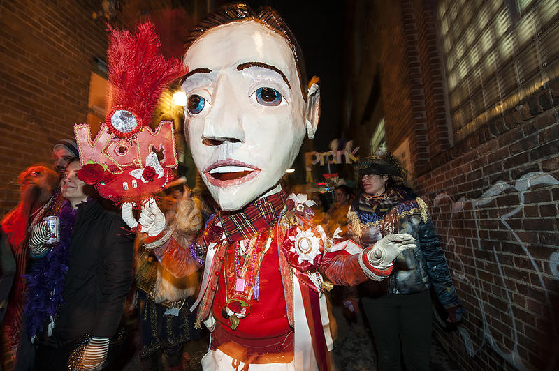 An outsized head tops an elaborate costume as paraders make their way down an alleyway.