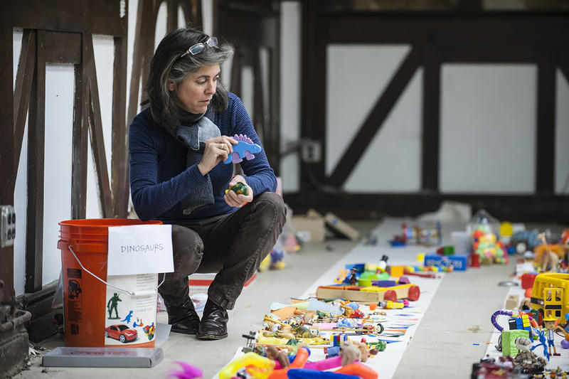 Sarah Lugg Regan eyes an array of toys organized artfully on paper as she decides where to place a plastic dinosaur.