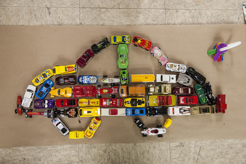 Matchbox cars are parked in the shape of a car.