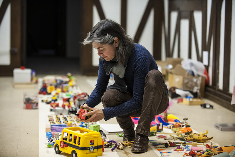 Lugg Regan squats between rows of toys, puzzling on where to put a piece..