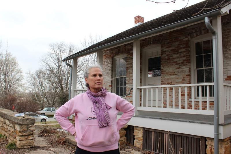 East Lawrence resident and artist Ardys Ramberg stands in front of the historic Murphy-Bromelsick House in Hobbs park. The neighbors fought to have it relocated to this site, instead of torn down.