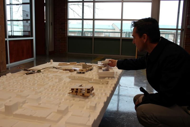French architect Charles Blanc of Sans Facon, the lead artists on the project, crouches to look at an architectural model of the 9th Street corridor.