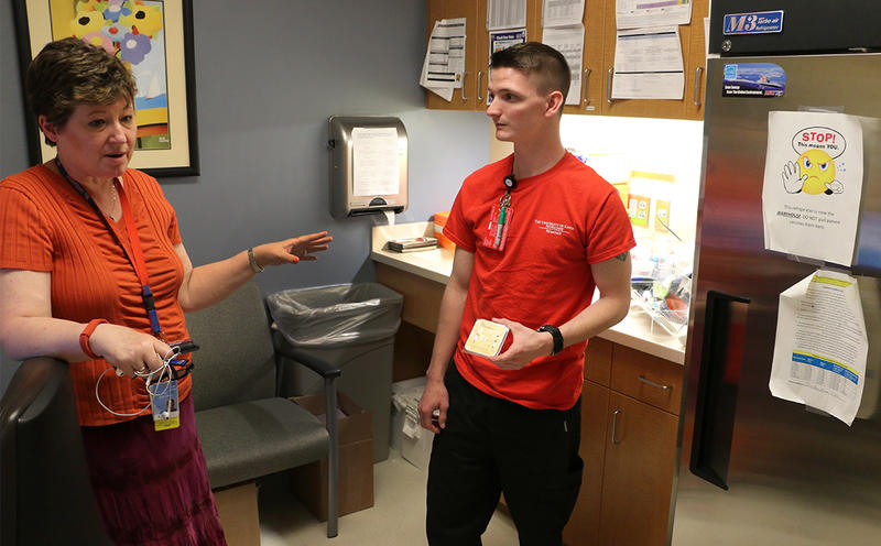 Dr. Pam Shaw, a pediatrician with the University of Kansas Hospital, discusses the importance of vaccinating adolescents against the human papillomavirus as medical assistant Travis Whaley looks on.