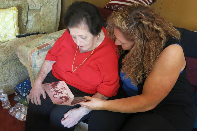 Regina Dollman, left, and her daughter, Lori, look at old family photos in the living room of their home in Kansas City, Missouri.