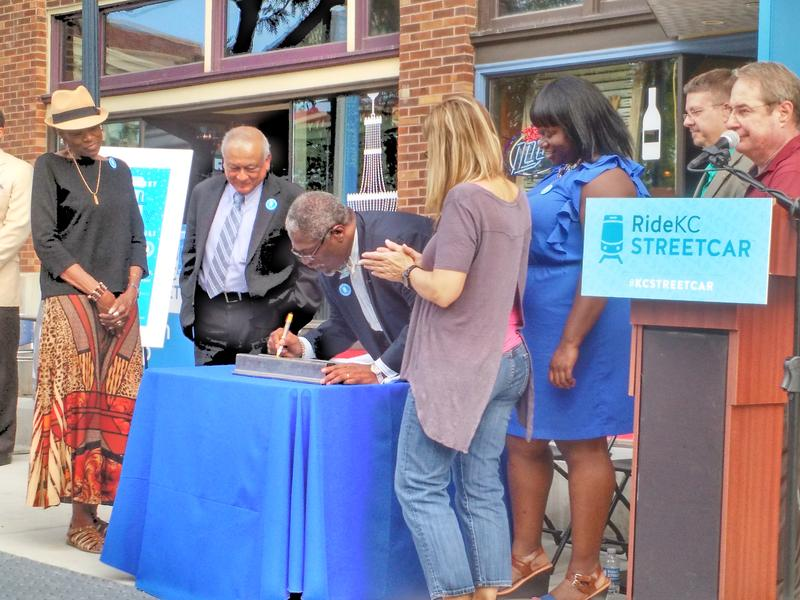 Mayor Sly James signs a commemorative piece of streetcar rail as city council members, old and new, watch. The signing was part of a 'Rail Rally' to celebrate the project's track completion.