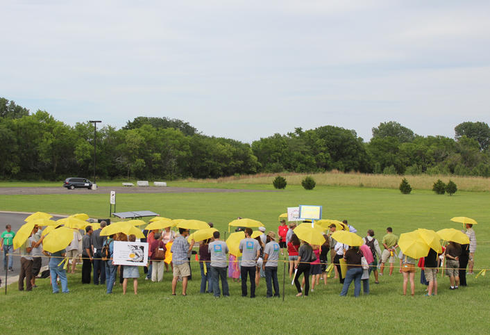 Participants in a rally Tuesday hold umbrellas to protest a proposal by Westar to make solar customers pay a higher monthly flat fee.