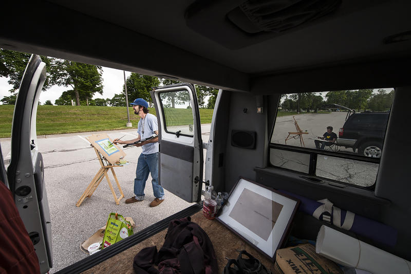 Working from a van filled with art supplies, Alex paints at his easel in the open air.