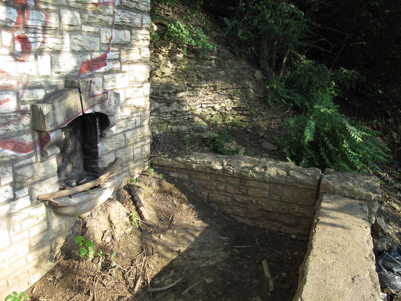 This old water fountain sits next to the stairs. The section of the staircase remains buried. More recently the now out-of-use water fountain seems to have been used as a fire pit.