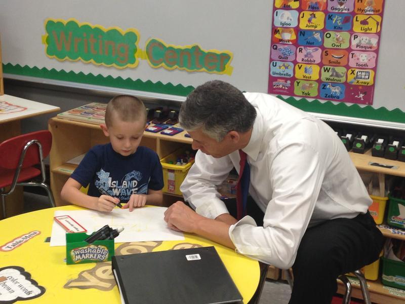 U.S. Secretary of Education Arne Duncan talks to a preschooler about his artwork during a visit to Kansas City, Missouri.