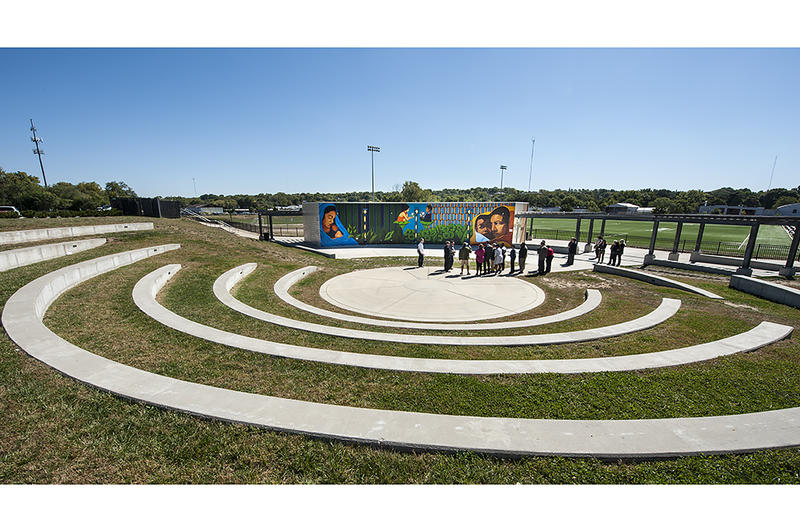 Concrete seating in the open-air amphitheater encircles the tour group at the athletic fields at 9th and Van Brunt.