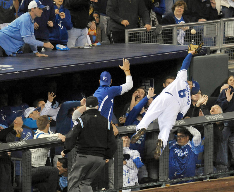 Kansas City Royals third baseman Mike Moustakas dives into the stands to catch a foul ball hit by Baltimore Orioles center fielder Adam Jones during the sixth inning in game three of the 2014 ALCS.