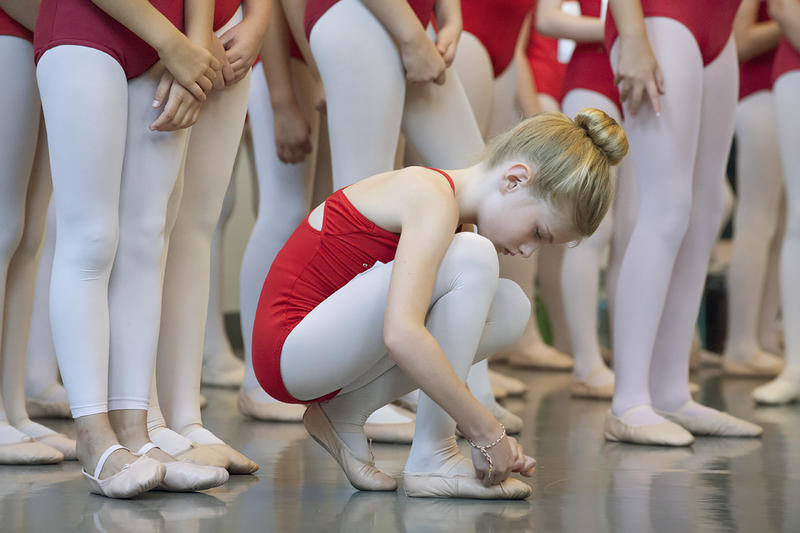 Nine-year-old Lily Migneron adjusts her shoe while waiting for her chance to impress the judges.