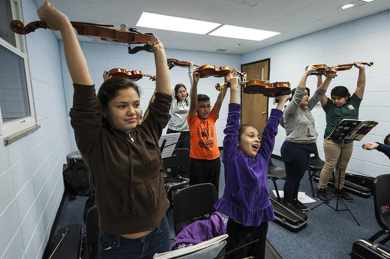 Emily Lopez, 11 (front left), Lizbeth Chavez, 8 (front center), and the rest of the Violin 1 class take a mid-lesson stretch.