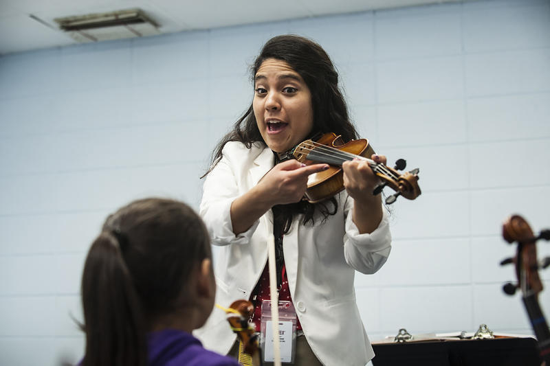 Lead Violin Teacher Selene Hernandez tests her students on proper arm positioning.