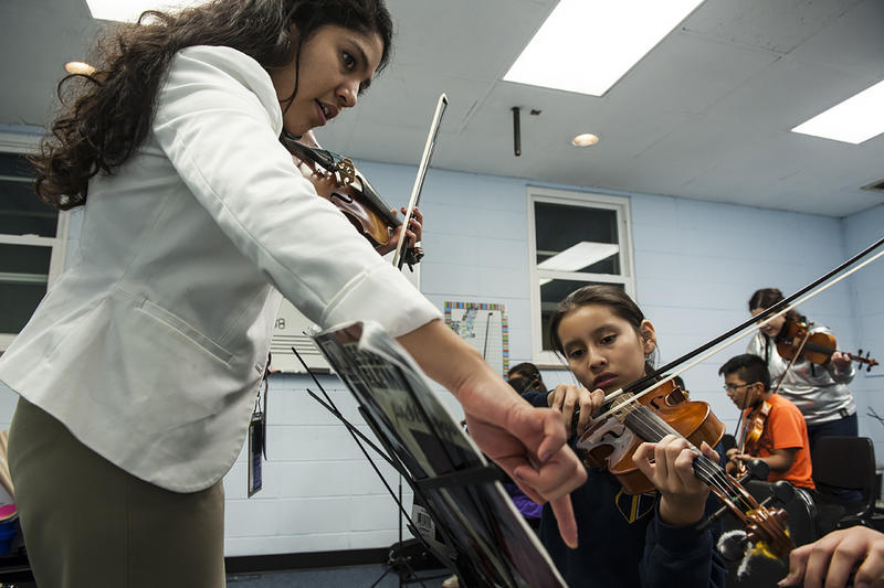 Moving from music stand to music stand, Hernandez keeps her students focused.