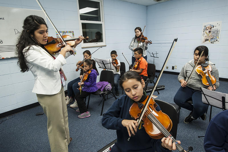 Hernandez looks over the shoulder of ten-year old Anaely Marquez as the class walks through a new piece.