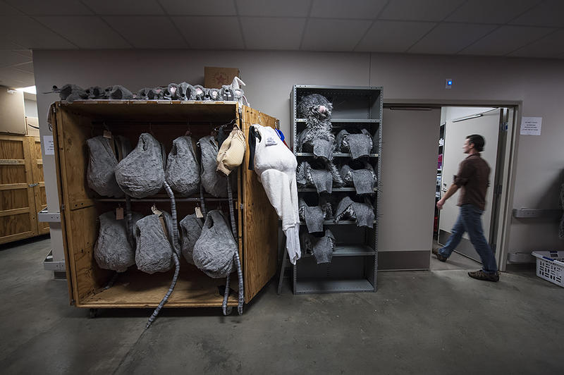 Backstage, large mouse costumes fill shelves as dancer Logan Pachciarz walks into a dressing room.
