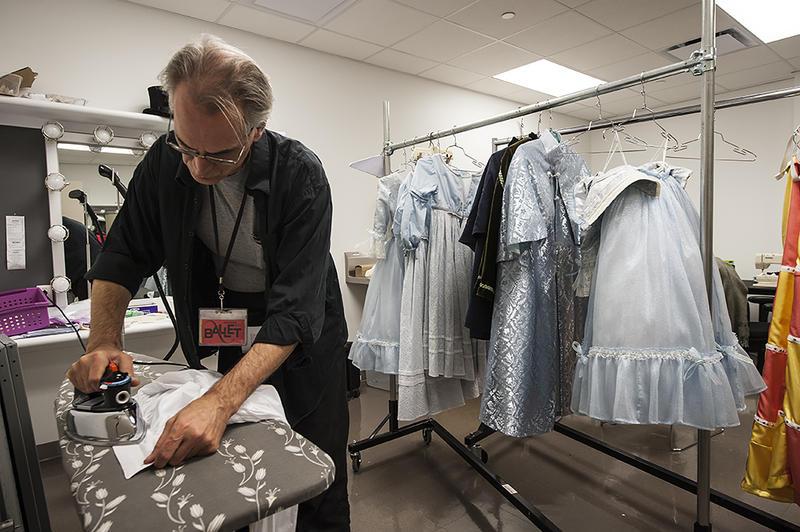 Dresser Shawn Sorrell spiffs up Dr. Drosselmeier's costume before sending him onstage.