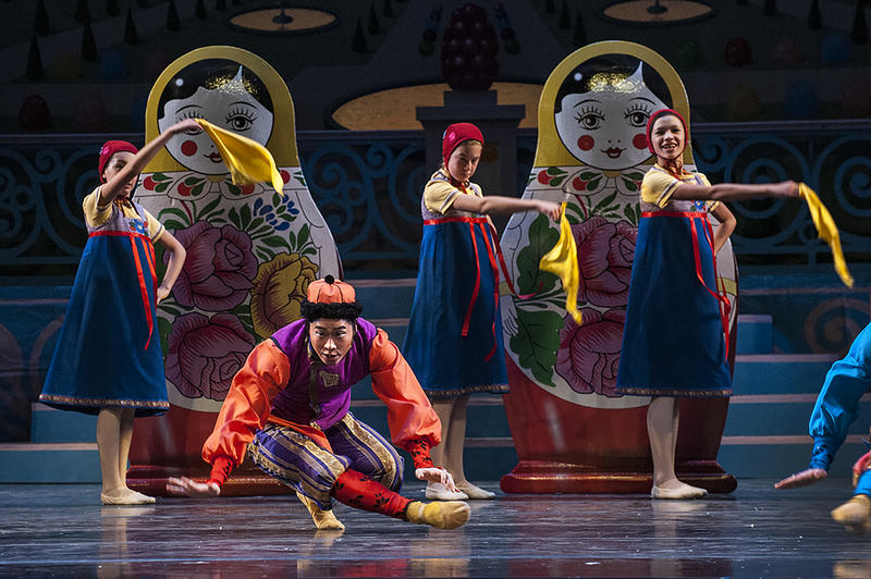 Large matryoshka dolls loom as Yoshiya Sakurai performs a Russian dance.