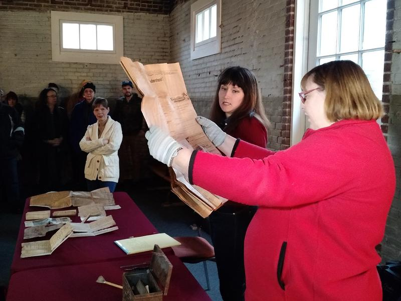 Denise Morrison (right) and Kate Warfield with the Kansas City Museum look at a newspaper from 1900 that was inside a time capsule found on the grounds of the recently demolished Thacher School in Northeast Kansas City.
